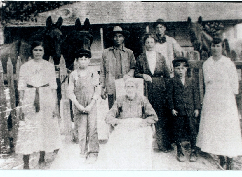 Serena Knight as an old woman, seated with her mixed-race family.